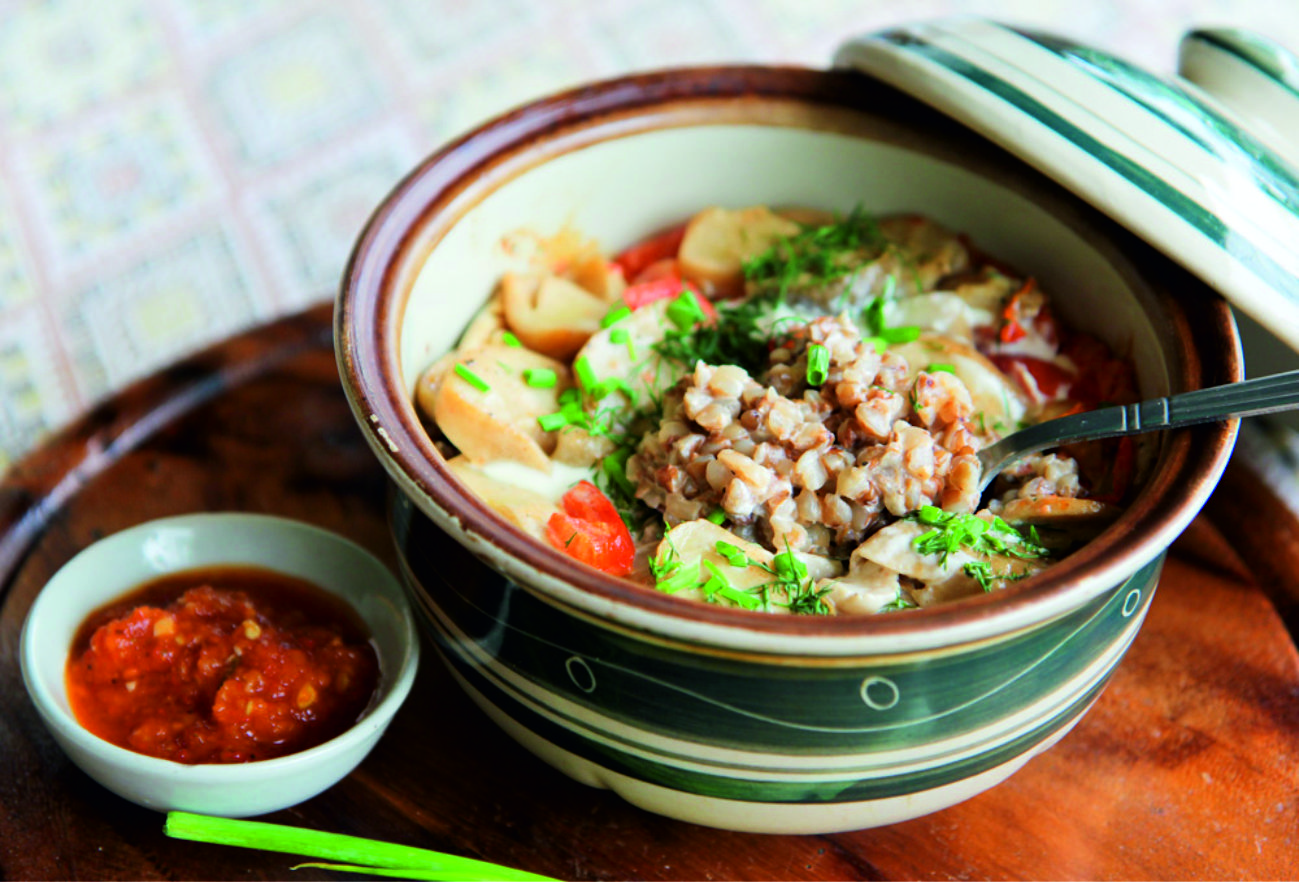 Traditional baked clay pot with buckwheat in cream milk and fillers on your choice
